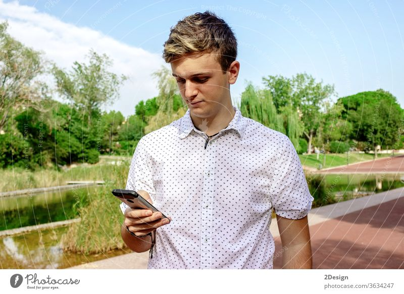 Young blond male using a cell phone outdoors 1 mobile young person teenage smartphone guy man people street fashion city lifestyle modern standing technology
