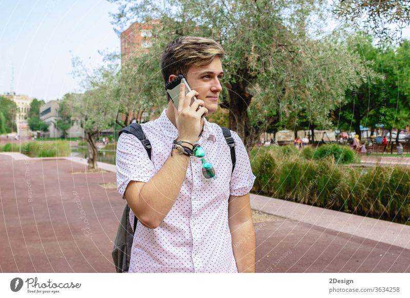 Young man using mobile phone while walking outdoors holding young 1 happy face person cool casual attire calling hispanic one person conversation adult modern