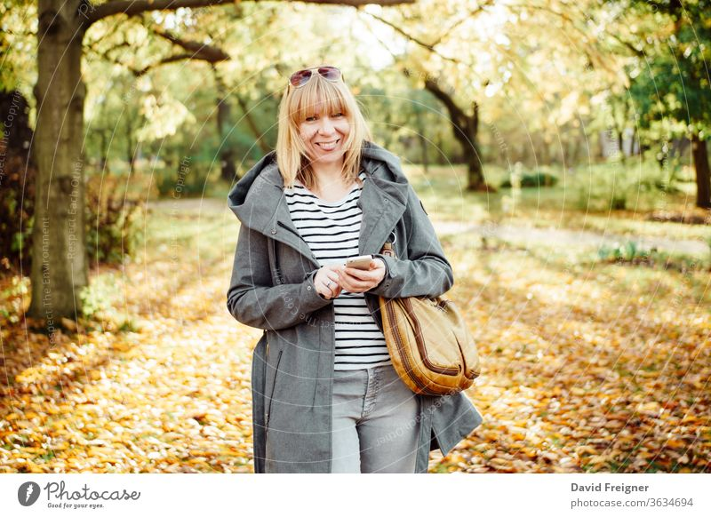 Happy blonde woman in a autumnal forest or park texting with her mobile phone. Communication, technology and outdoors concept. beautiful female happy person