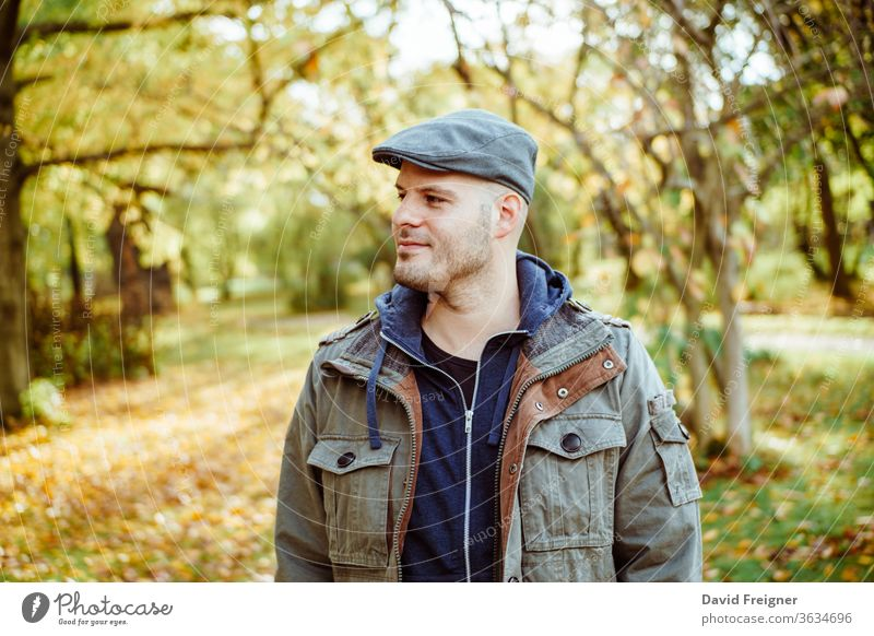 Man standing in a autumnal forest or park. Autumn, outdoors and lifestyle concept. people nature young person handsome fall male portrait man happy season