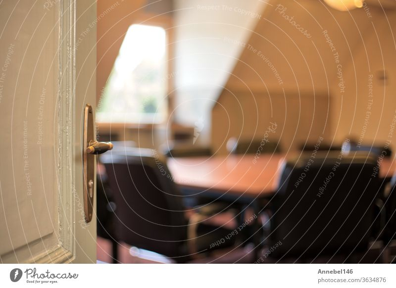 Door with handle opening to a blurred modern meeting room, office concept background interior business design inside door glass chair desk corporate conference