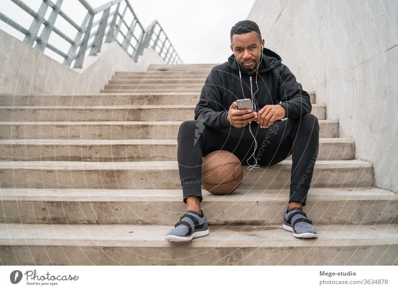 Athletic man using his mobile phone. sportsman runner listening earphones workout exercise lifestyle adult health outdoor training athletic guy communication