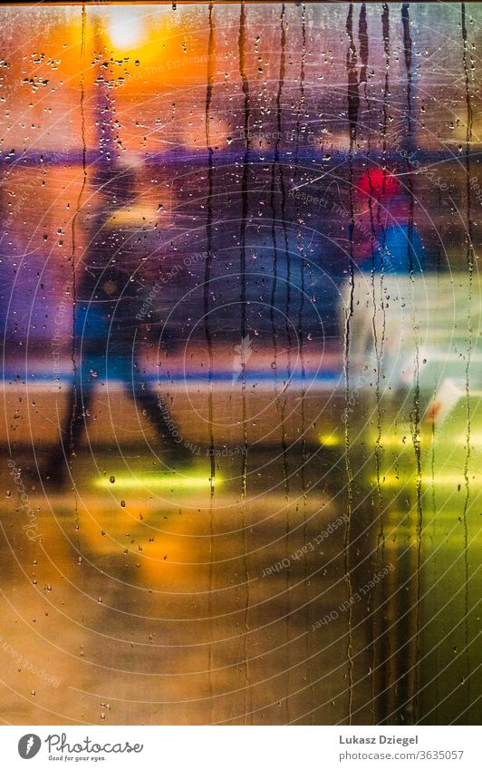 Window with raindrops and city lights with one person in the background closeup texture unrecognizable silhouettes move impressionism lifestyle windshield urban