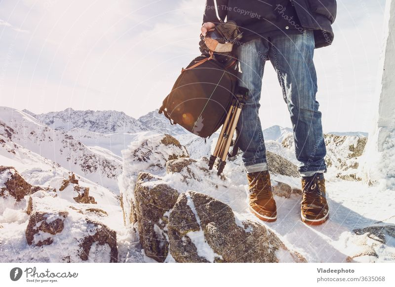 Photographer traveler on a mountain top with equipment in hands photographer blogger man leg foot rocks range freedom independence courage fashion lifestyle