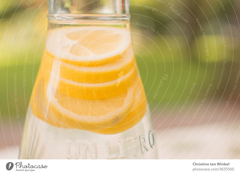 bright yellow slices of lemon in a carafe filled with water. Weak depth of field, green areas in the background Lemon slices water carafe Water Drinking water