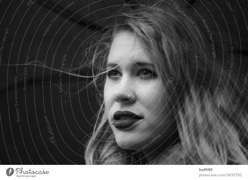 The young woman under the umbrella in wind and weather looks into the distance portrait Woman Young woman Face of a woman blurred background 18 - 30 years