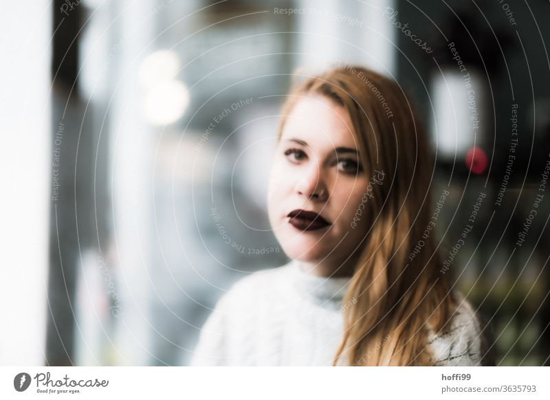 the young woman looks into the camera Face of a woman Woman Young woman blurred blurred background portraite Adults 18 - 30 years Human being