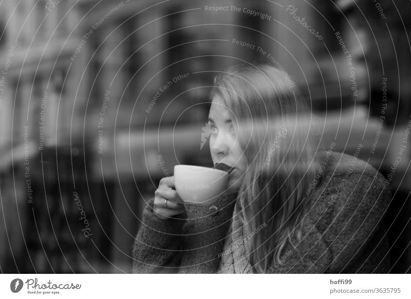 the young woman drinks coffee and looks through the window to the other side of the street To have a coffee Face of a woman Woman Young woman street coffee