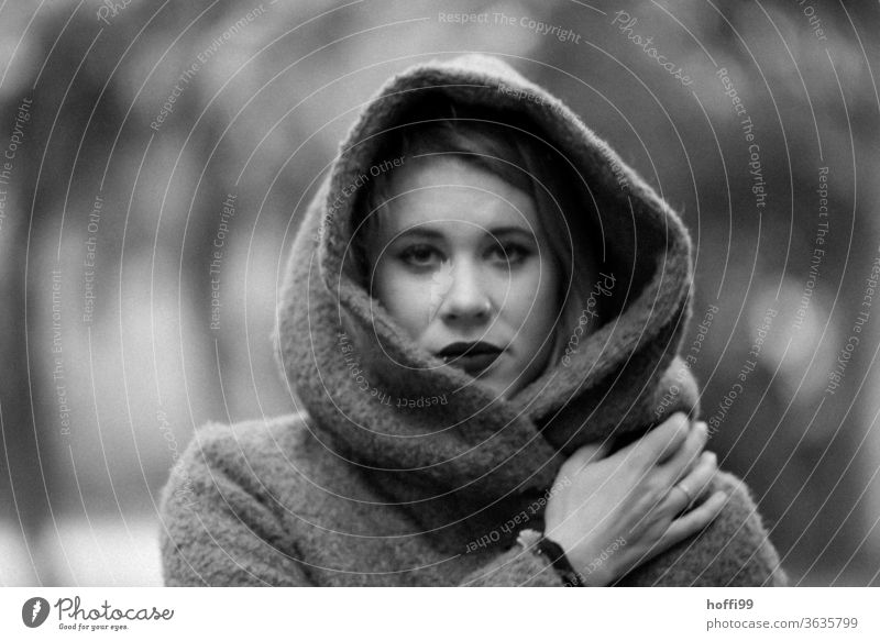 The young woman in the coat with hood looks into the camera portrait Woman Young woman Face of a woman blurred background 18 - 30 years Adults portraite