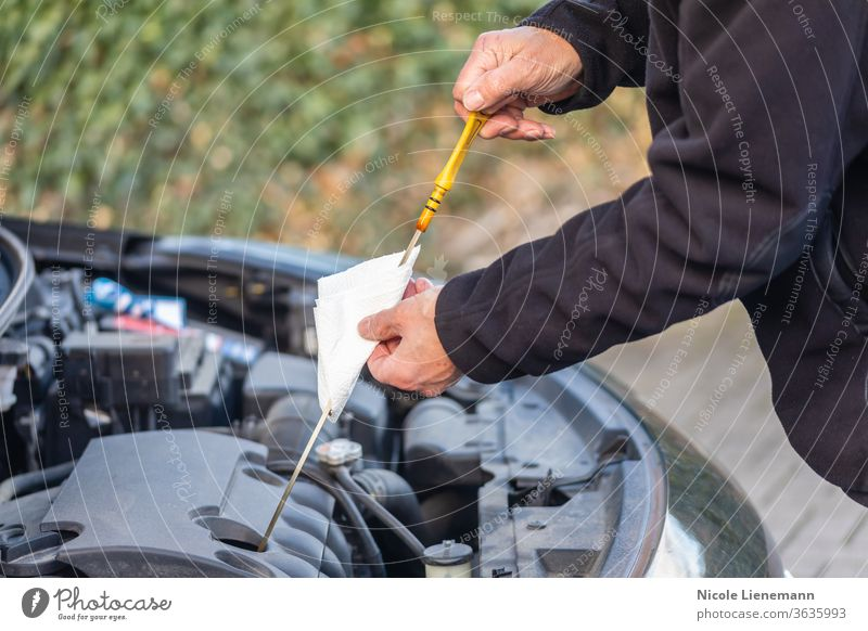 Man is checking oil level on car drive cars black petrol fuel shopping filter gas hand handy industry maintenance motor vehicle man mechanic mechanical men