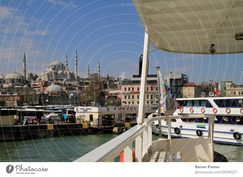 Istanbul, Turkey, 8 April 2015: A ferry approaches the station on a sunny day, revealing a beautiful view on the skyline of Istanbul. blue boat bosporus