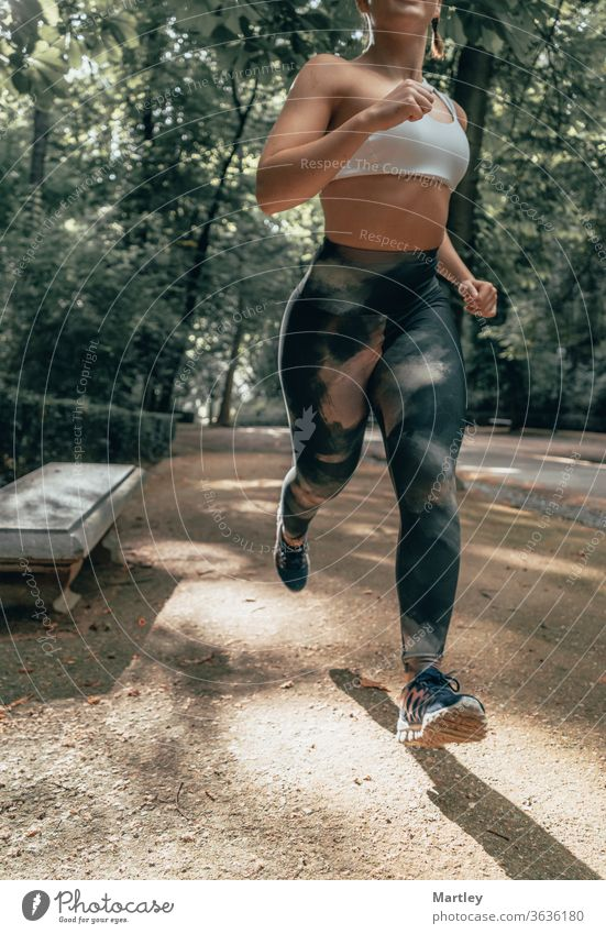 Body of a fit woman running through a park in summer. Fitness model outdoors in nature. Concept of getting fit, losing weight and healthy life sport fitness