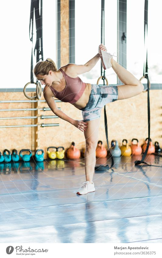 Young sporty woman stretching legs in the gym active activity adult aerobics athlete athletic attractive beautiful blonde body caucasian energy exercise female