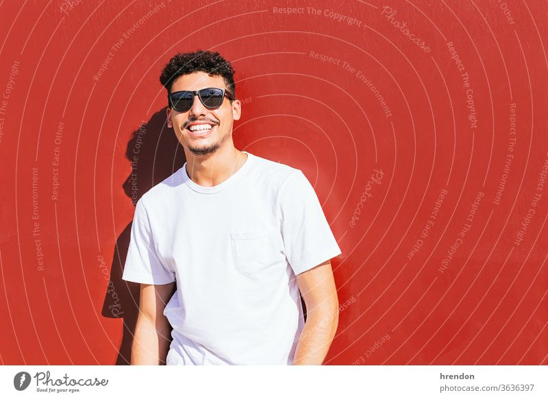 portrait of a young man with sunglasses smiling on a red wall male guy smile lifestyle happy attractive happiness posing beard positive leisure nature cool