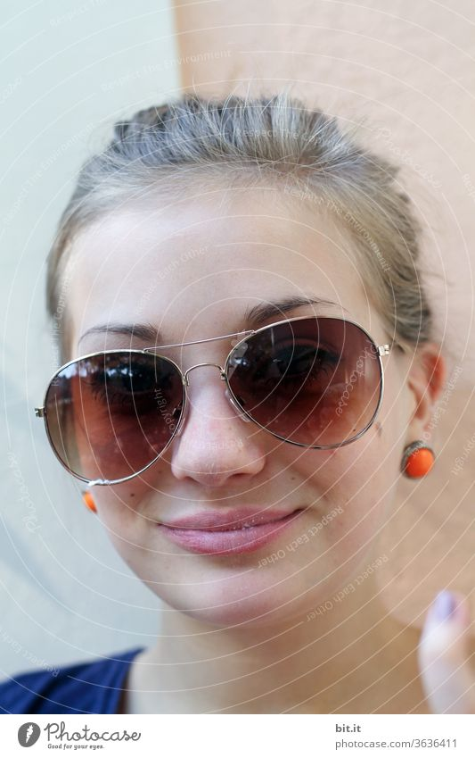 Teenager in front of a Mediterranean wall with orange earrings, ponytail and sunglasses. Teenager with blond hair smiles into the camera. Holiday photo of a young woman in summer, in front of a light-coloured facade, wall. Sun protection through crooked sunglasses.