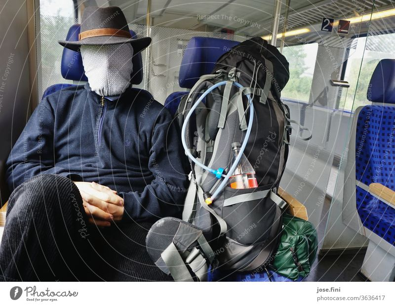Train journey in corona times Young man go by train Track public transportation Sit Wait Backpack Backpacking Mask covering coronavirus Faceless Passenger