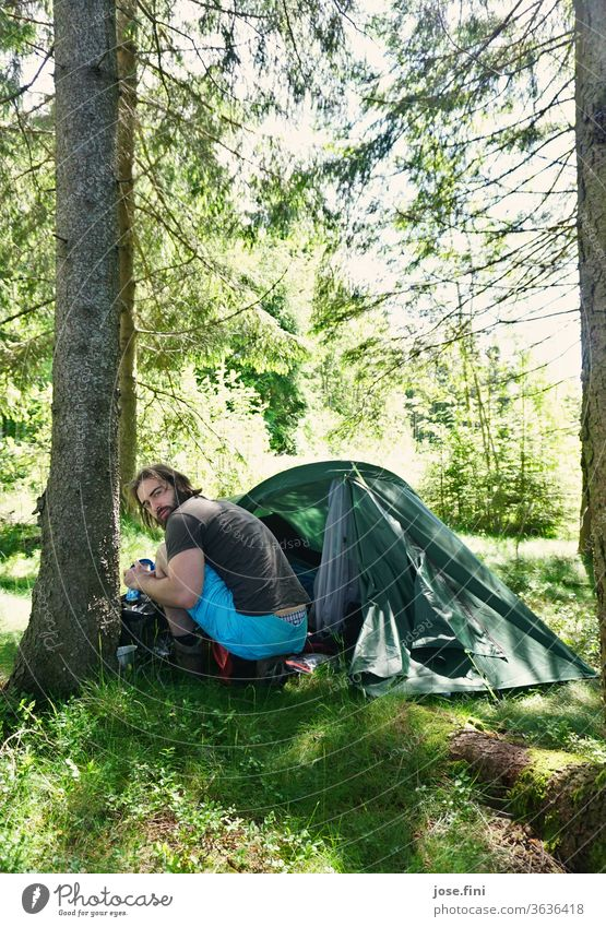 Man sits in the forest in front of a tent and looks back into the camera. Young man Tent Forest Morning Summer Sunlight Nature Adventure Vacation & Travel