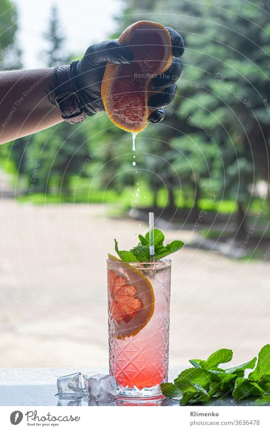 A refreshing summer cocktail with a slice of grapefruit. Alcoholic drink Paloma. Decorated with a sprig of mint and ice cubes. alcohol aperitif heat crush drops