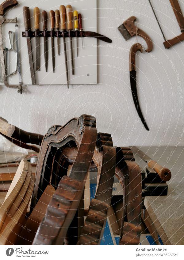 Stühle in einer Werkstatt Stuhl Restaurator restaurieren Werkzeug Holz Holzstühle Säge alt Epoche Epochen schleifen Atelier Holzstuhl Detail Innenaufnahme