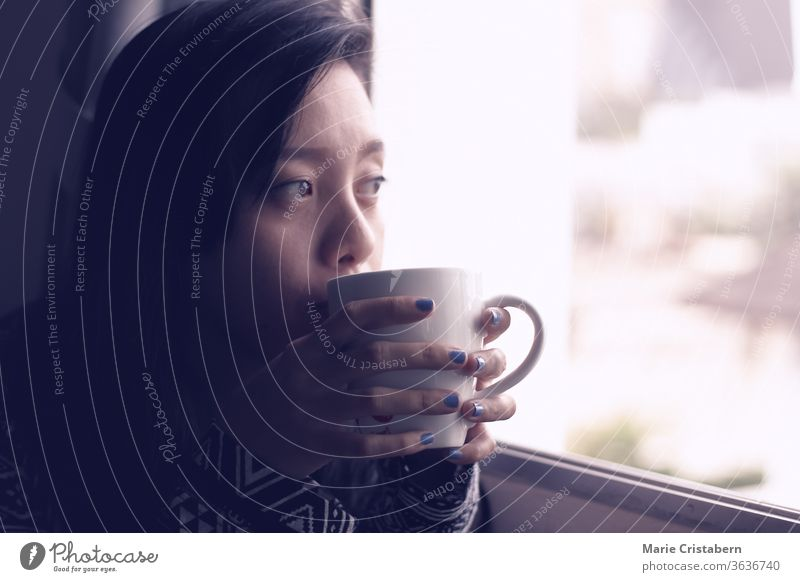Asian girl having coffee on an early autumn morning beside the window, shows concept of new normal, home quarantine and self isolation during covid-19 pandemic