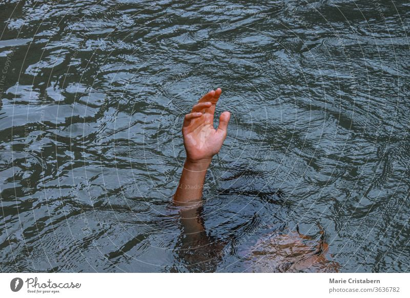 A hand reaching out from under the water to show the concept of drowning, mental health crisis, depression and struggle mental health crisis concept
