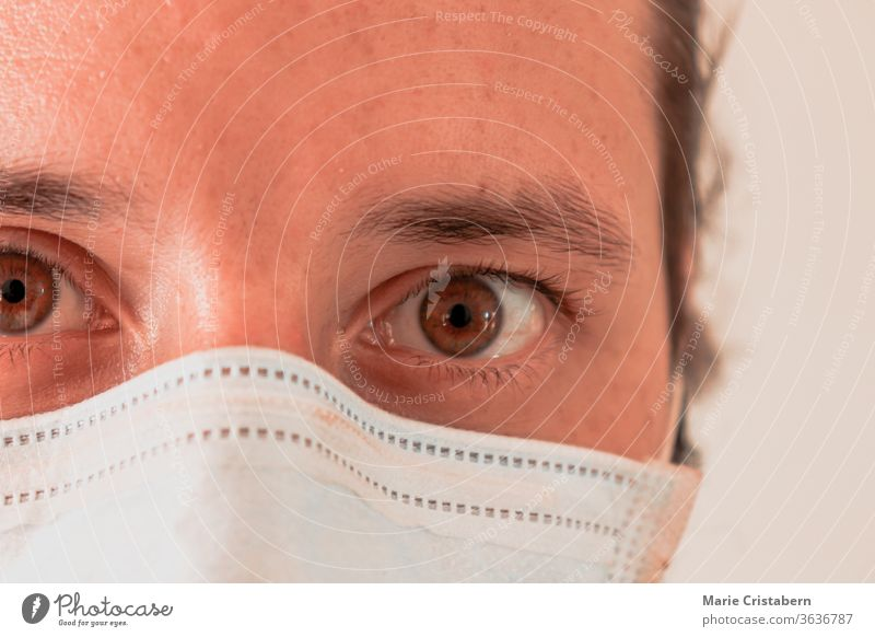 Close up of an overworked male nurse wearing a surgical mask Male nurse Caucasian male Eyes wide open Covid-19 pandemic Essential worker Healthcare professional