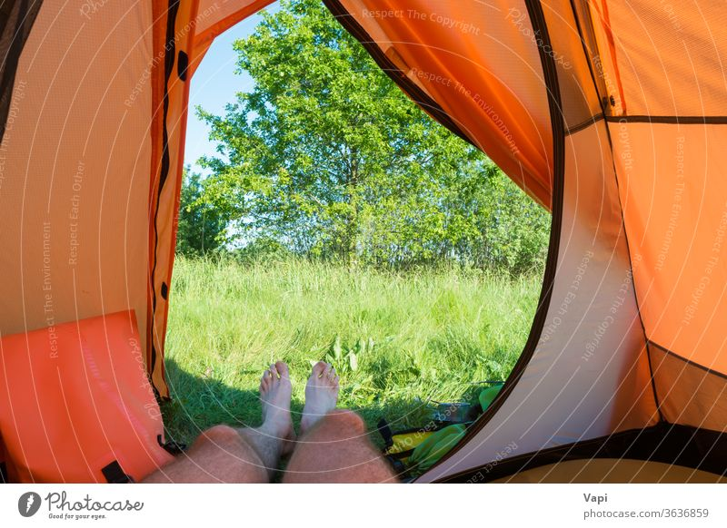 Man resting inside orange tent camp vacation camping legs nature view grass foot people recreation forest tree landscape adventure tourism summer travel hiking