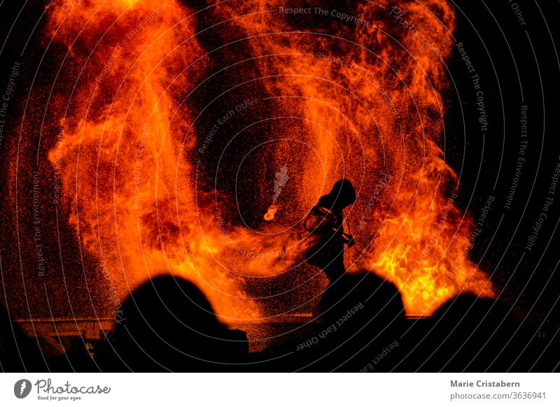 Silhouette of a firefighter fighting to contain a raging fire as a crowd looks on saving lives essential worker everyday hero firefighting disaster ablaze