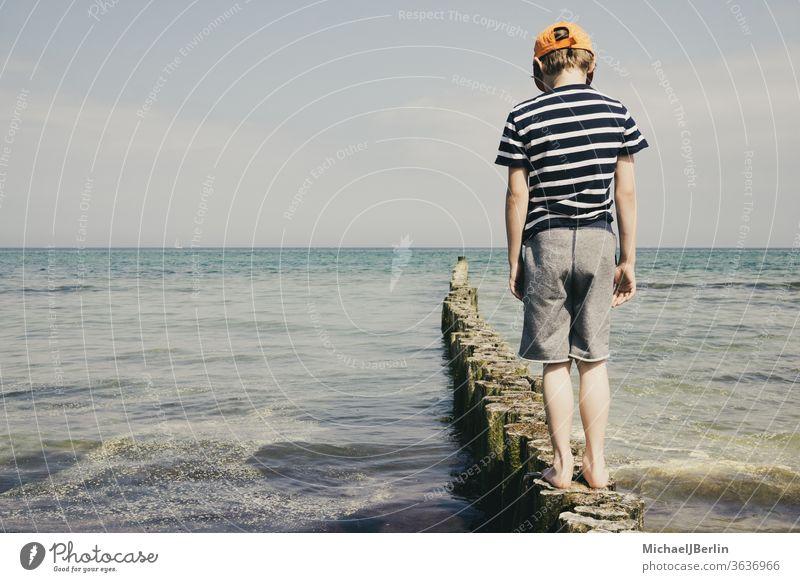 Boy at the Baltic Sea stands on bollards Ocean Boy (child) Schoolboy Child children holidays vacation East Germany Rostock Warnemünde pollster Balance Joy fun
