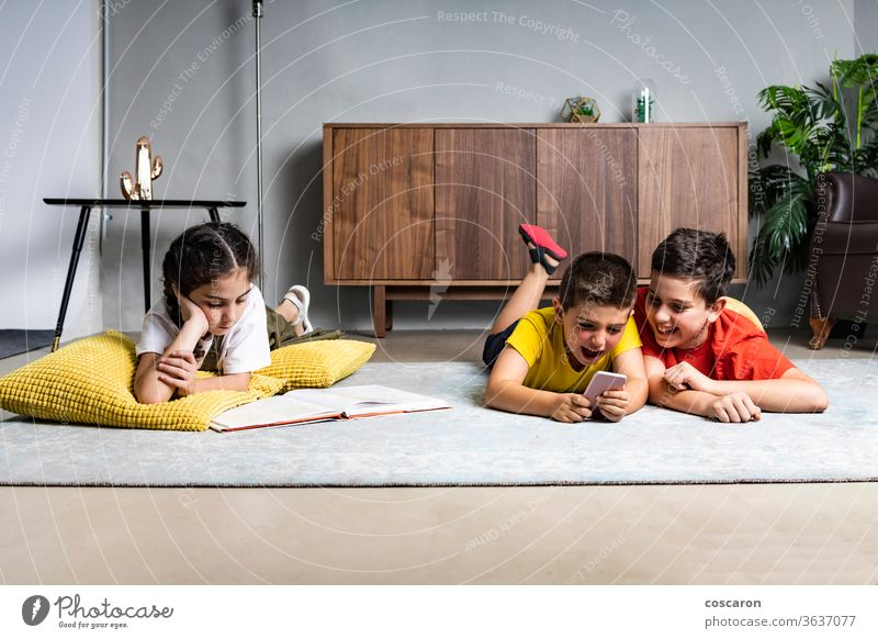 Little girl reading a book while two boys playing with a smart phone brothers cell phone cheerful child childhood children communication cute data different