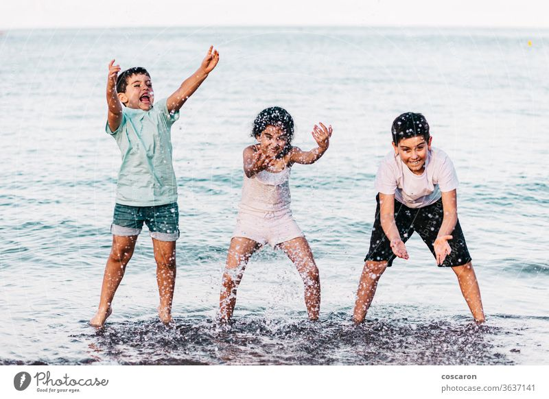 Three kids playing with the water on the beach action active beautiful blue boy bright cheerful child concept drop enjoy fresh fun funny girl happiness happy