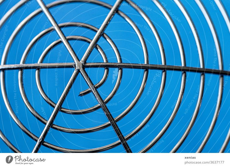 Symmetry / Snail-like windings of a stainless steel skimmer in front of a blue background Slotted spoon Spaetzle lifter Noodle helper High-grade steel Round