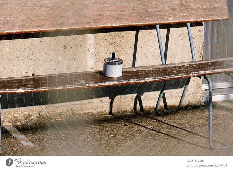 A smoking area in the sun: brown wooden bench, stars on the ashtray, lots of sun and long shadows on the floor Ashtray asterisk Wooden bench seat Old Brown