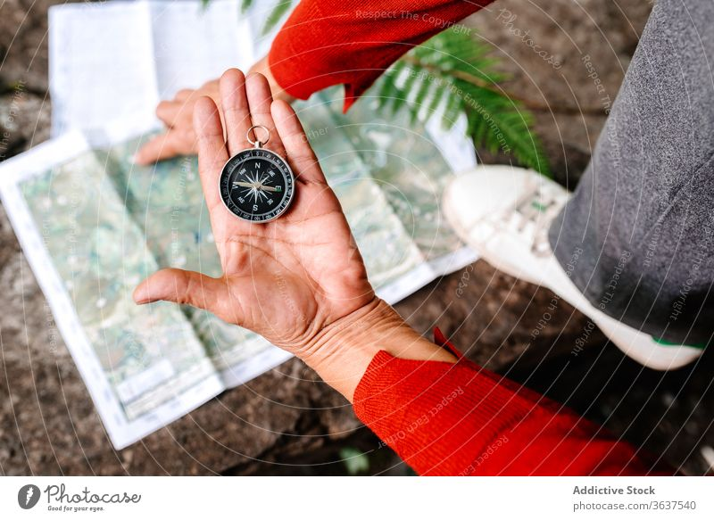 Crop elderly woman navigating with compass and map navigate orientate traveler forest read tourist female adventure trip vacation tourism rock explore journey