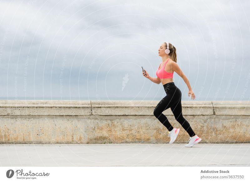 Fit jogger in headset running on embankment with smartphone headphones sport workout training sportswear sky cloudy slim activity sportswoman listen music