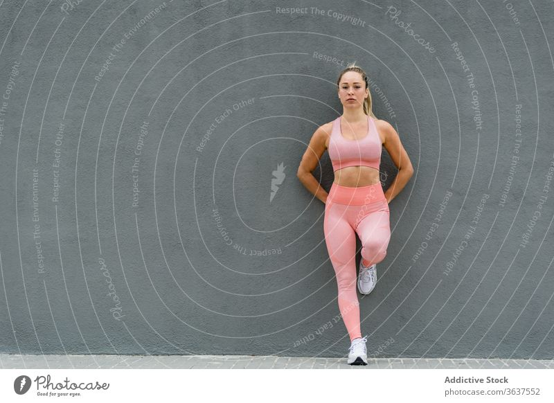 Sportswoman in active wear standing leaned on gray wall sportswoman lean on leg fit healthy wellbeing activewear harmony vitality leggings sneakers embankment