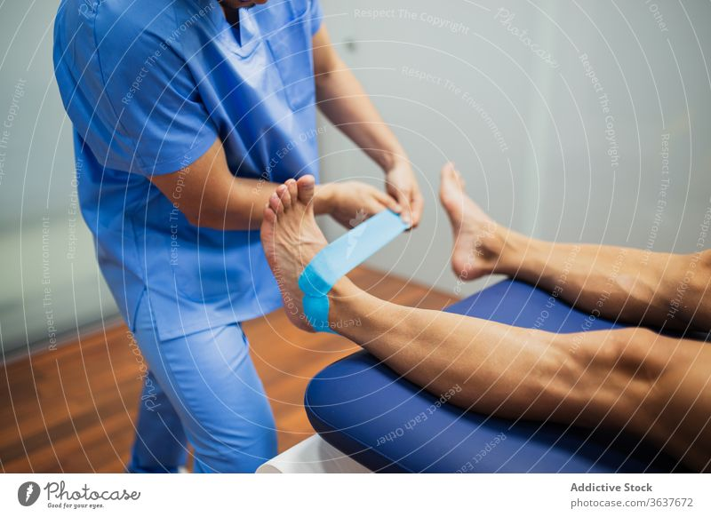 Crop anonymous osteopath putting elastic tape on foot of patient chiropractor kinesio recovery health care assistance feet uniform professional attach