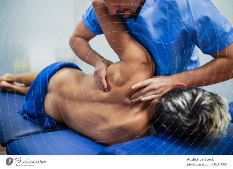 Orthopedist raising arm of sportsman during medical checkup orthopedist patient recovery examine back professional osteopathy aid health care rehabilitation