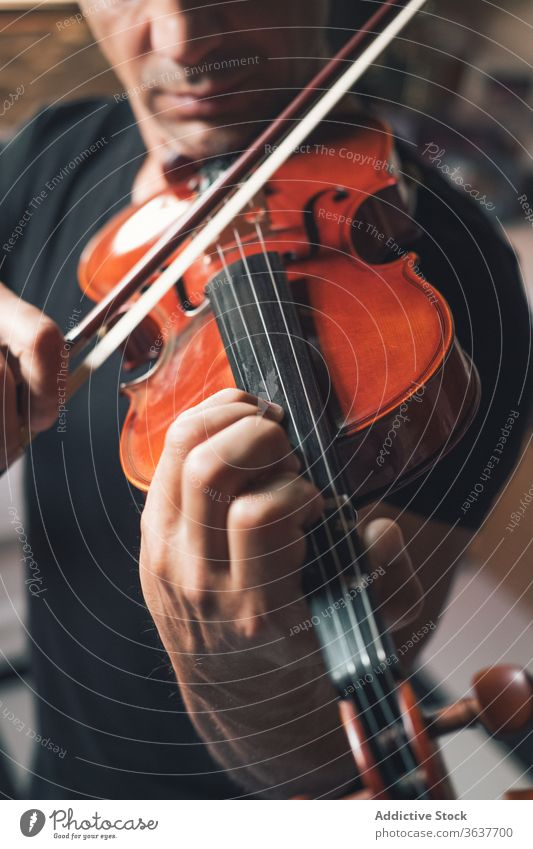 Anonymous male musician playing violin instrument man talent sheet violinist melody ethnic hispanic perform rehearsal sound entertain tune hobby rhythm player