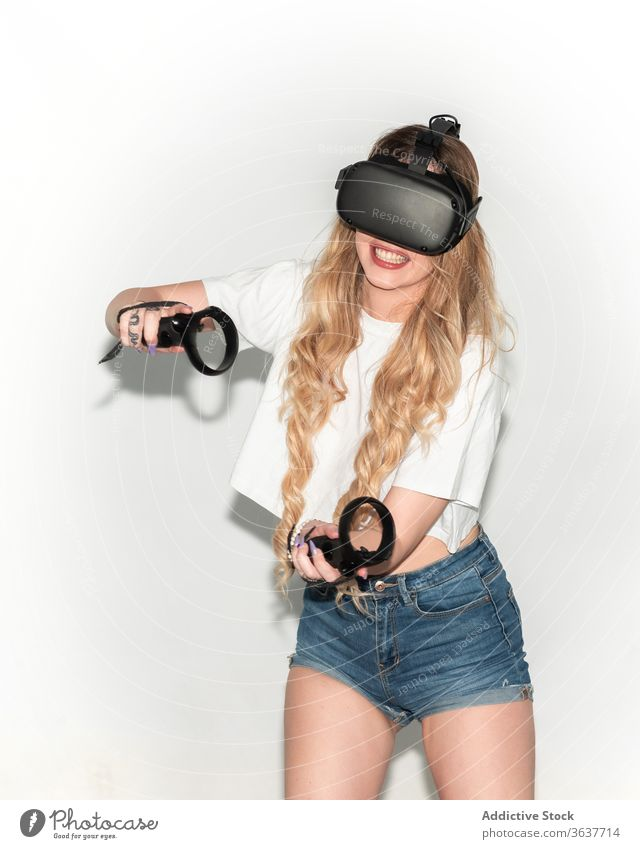 Content woman playing game in VR headset vr virtual reality video game controller goggles studio entertain female excited experience simulate futuristic modern