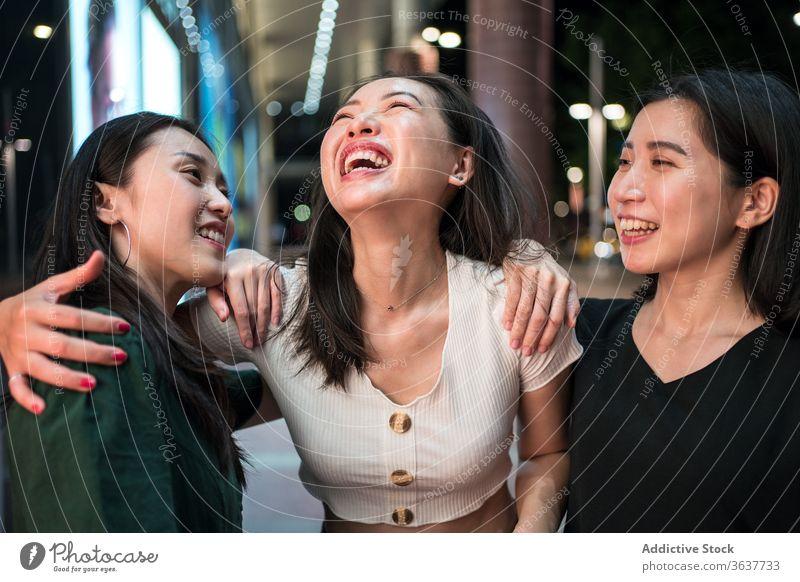 Cheerful ethnic women talking on street company laugh together girlfriend stroll city night cheerful humor friendship asian walk relationship smile joy urban