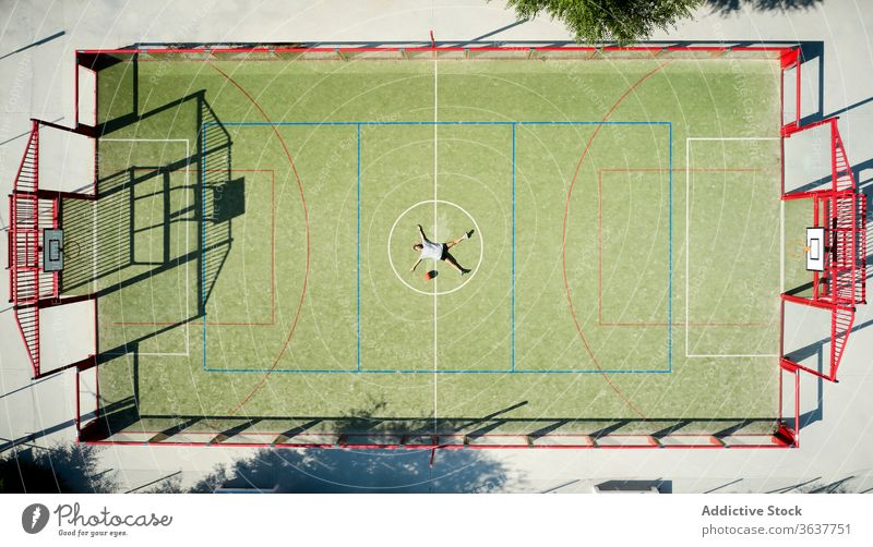 Basketball player relaxing on playground basketball woman rest lying tired sport court sportswoman circle athlete sportswear training activity game workout