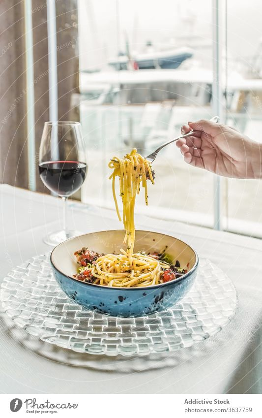 Crop person having pasta and glass of wine meal red wine home gourmet eat delicious dinner drink food beverage alcohol fork vegetable sauce simple italian