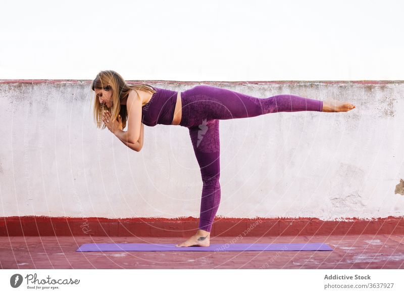 Calm woman practicing yoga in Warrior position warrior pose practice balance namaste gesture healthy mat terrace female harmony asana concentrate meditate