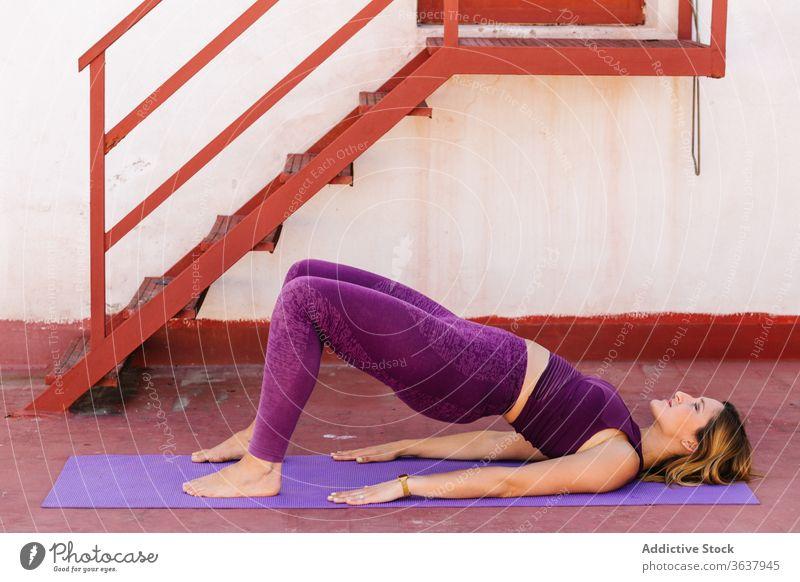 Tranquil woman practicing yoga in Bridge asana bridge pose balance activewear lying calm harmony setu bandha sarvangasana female tranquil serene meditate