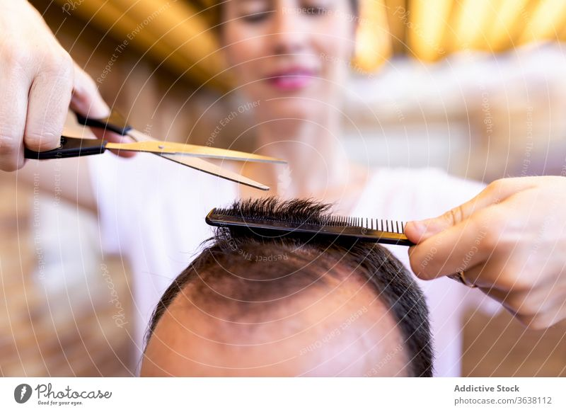 Female barber cutting hair to crop unrecognizable man in barbershop hairdresser trim client scissors comb haircut master profession workplace sharp accessory