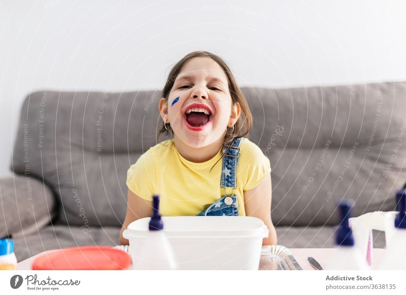 Expressive girl with dirty finger sitting on sofa at home grimace expressive mouth opened playful diy creative domestic child denim overall colorful amazed