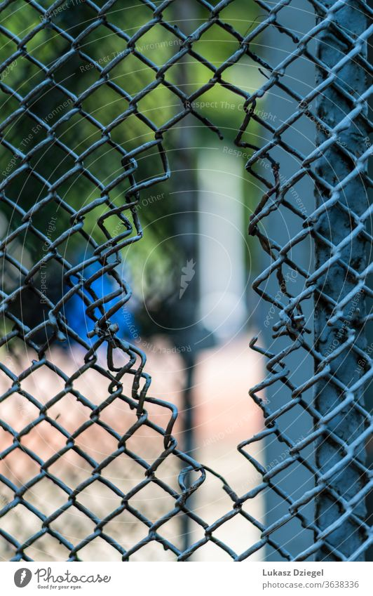 Hole in a mesh fence through cut dangerous sharp damaged boundary steel wired pattern barbed industry protection cage security barrier hole metal chain broken