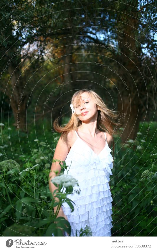 Blond haired lady dancing in the woods in white summer dress with her hair windswept. Emotional and natural image with copyspace. messy hair alone loneliness