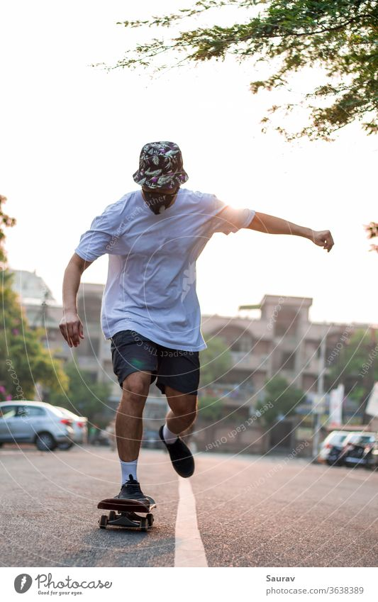 Front view of a young adult skateboarding on an empty street while wearing a protective mask during sunrise. summer recreation covid-19 new normal outdoors